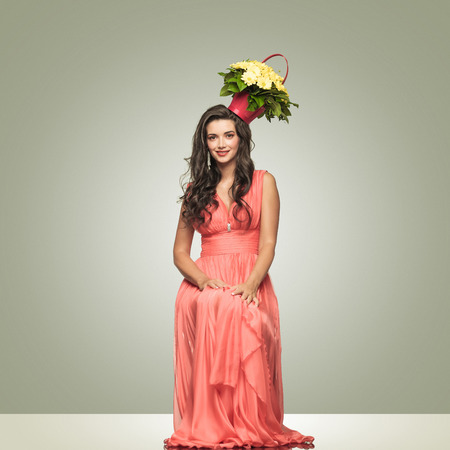 elegant happy lady in red dress with flower basket on her head is smiling to the camera on grey studio background photo