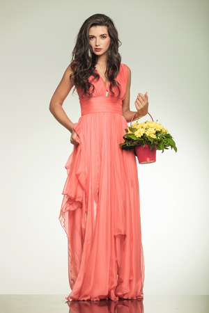 full body picture of an elegant woman in red dress holding a flower basket and pulls up her dress on grey background photo