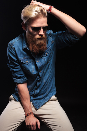 man with long hair: Cool fashion man with long red beard wearing blue shirt and sunglasses, sitting and fixing his hair. On black background. Stock Photo