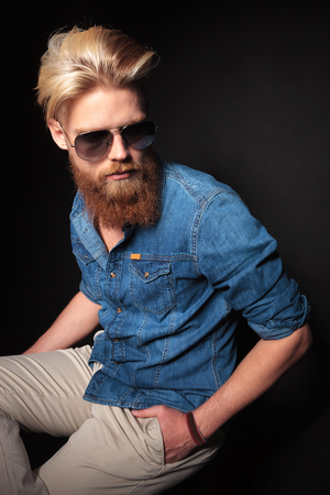 Angle view of a handsome fashion guy wearing a blue shirt and sunglasses, sitting with his hand in pocket, looking away. photo