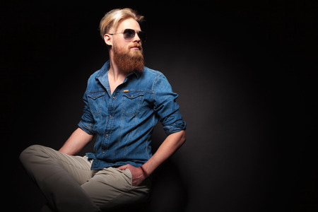 Attractive fashion man with long red beard sitting with his hands in pocket, looking up. Copy text space.