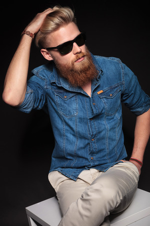 Fashion man in blue shirt and black sunglasses sitting on a white chair while fixing his hair. photo