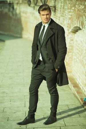 ragazze bionde: Vista laterale di un elegante uomo d'affari su un marciapiede con la mano in tasca, guardando la telecamera. Look vintage.