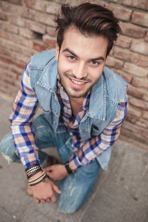 Above view of a attractive young man sitting on the side walk near a brick wall, looking at the camera photo