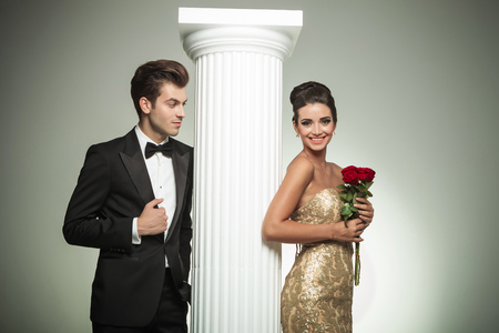 elegant man in tuxedo looking at his laughing woman near column , she holds red rosed photo