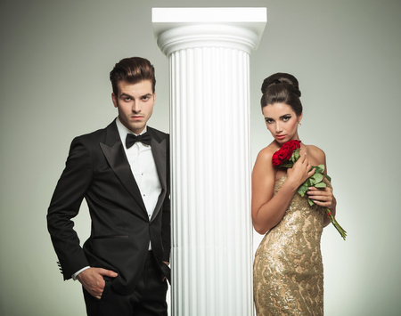 elegant young couple posing near column, woman is holding roses photo