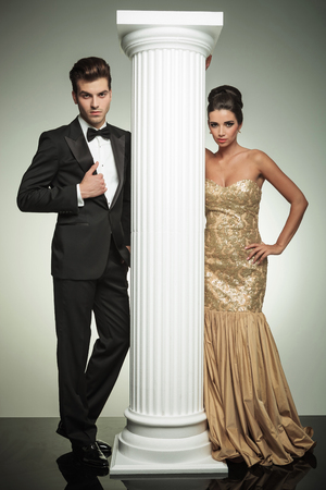formal man and woman in evening clothes posing near column in studio photo