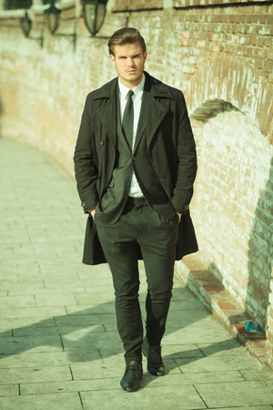 Full length picture of a elegant business man on a sidewalk near a brick wall holding his hands in pocket. Vintage look. photo