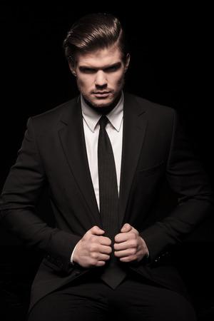 hombre sentado: Hombre de negocios elegante sentado y tirando de su chaqueta, mirando a la cámara. En fondo negro.
