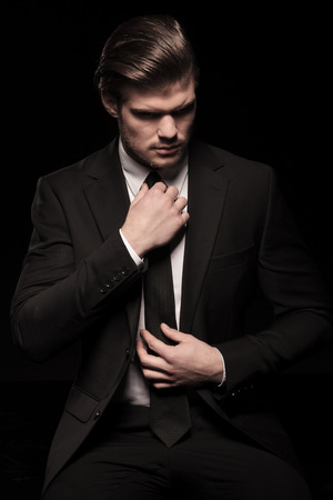 Picture of a elegant business man looking down while fixing his tie. On black background. Imagens