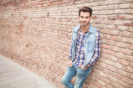 man side view: Angle view of a young casual man smilling, leaning on a brick wall with his hand in the pocket.