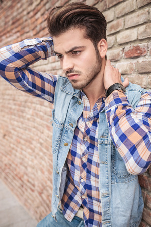near side: Side view of a young man leaning on a brick wall holding his hand on his neck, looking away from the camera