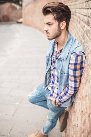 full lenght picture of a handsome casual man leaning on a brick wall with his hand in the pocket, looking away from the camera. photo