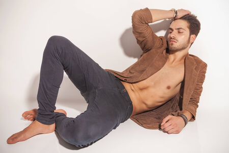 lay down: Young fashion man resting on the floor with one hand in his hair, looking away from the camera. on white background