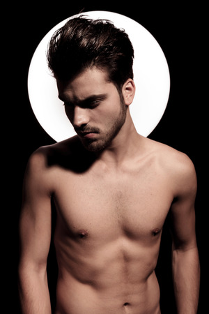 portrait of a naked fit young man with light aura, looking away to side photo