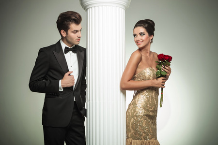 young elegant couple looking at each other near column, studio picture photo
