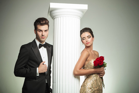 elegant couple posing near column, man in tuxedo and woman in evening gown with eyes closed photo