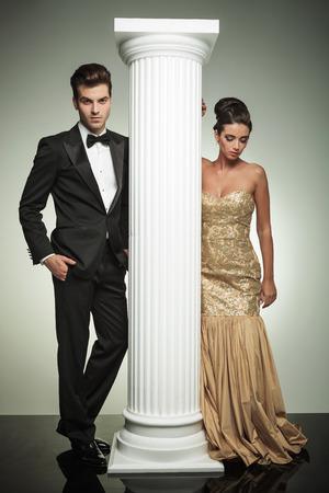 attractive elegant couple posing near column in studio, woman looking down photo