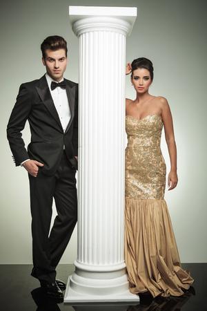sexy business women: luxury couple posing in studio near column, ceremony concept