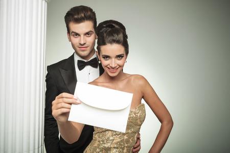 traje de gala: feliz pareja joven que presenta una invitación a su boda, sonriendo nar una columna en el estudio Foto de archivo