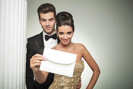 formal dress: happy young couple presenting an invite to their wedding, smiling nar a column in studio Stock Photo