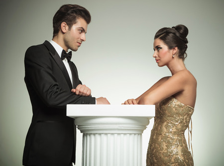 sexy bride: happy man and woman in evening clothes lean on a column and look at each other in studio