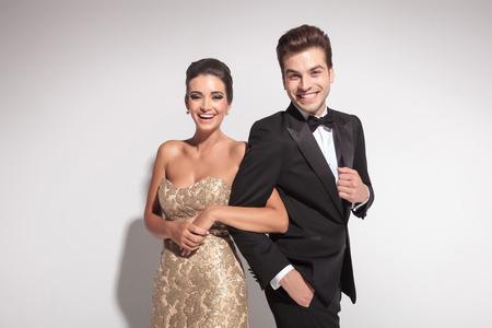 エレガントなカップルが腕と腕を押しながらカメラの笑い。灰色の背景。