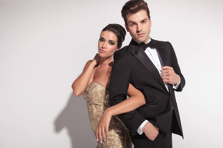 business dress: Elegant woman wearing a golden dress holding her man by arm and both posing in studio.