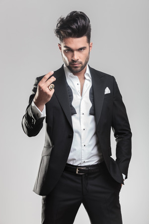 Elegant young man in tuxedo looking at the camera while snapping his finger and holding one hand in his pocket.  Foto de archivo