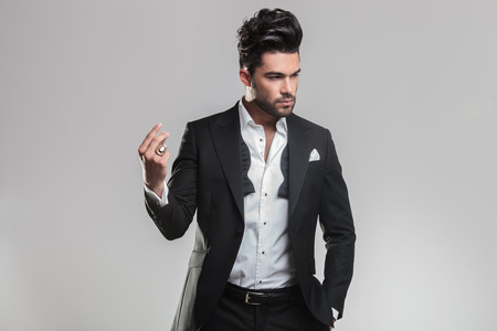 Handsome young man in tuxedo snapping his finger while looking away from the camera. On grey background. photo