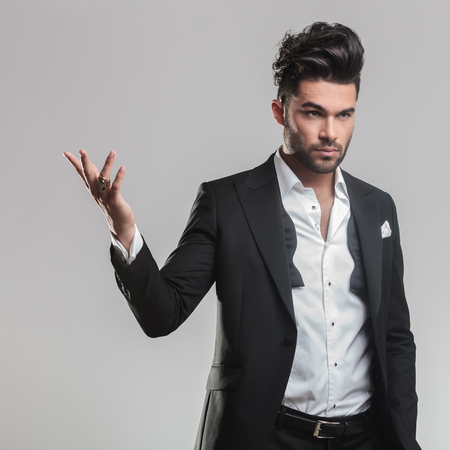 Close up of an elegant young man in tuxedo holding one hand in the air while looking away from the camera. On grey background. photo