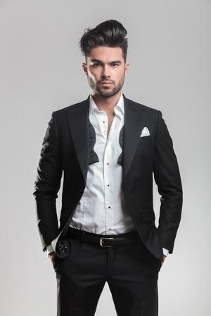 Мода молодой человек в смокинге, глядя на камеру при проведении его руку в карман. На сером фоне. Фото со стока