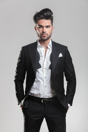 Fashion young man in tuxedo looking at the camera while holding his hands in pocket. On grey background. Stock Photo