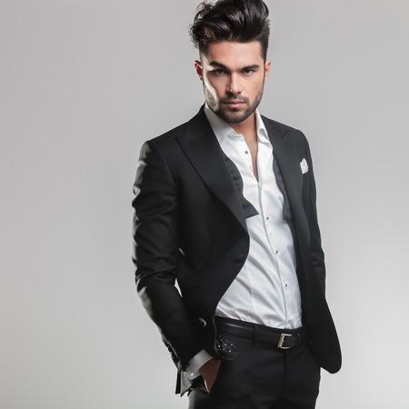 Beeld van een elegante jonge man in smoking te kijken naar de camera terwijl zijn handen in de zak. Op een grijze achtergrond
