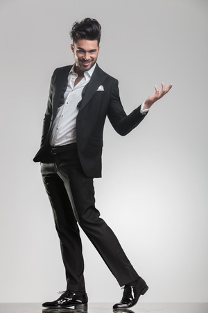 hand in pocket: Full length image of a elegant man walking while holding one hand in the air and the other in his pocket.