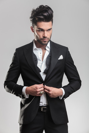 Close up picture of an elegant young man in tuxedo closing his jacket, looking away from the camera. On grey background. photo