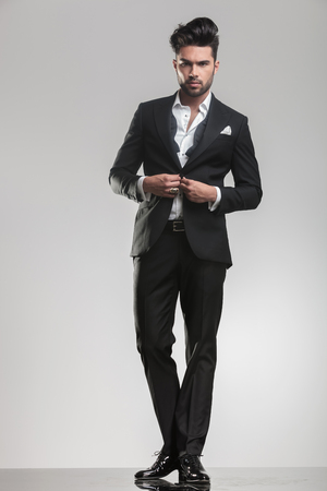 undone: Picture of an elegant young man ajusting his tuxedo while looking at the camera. On grey studio background. Stock Photo
