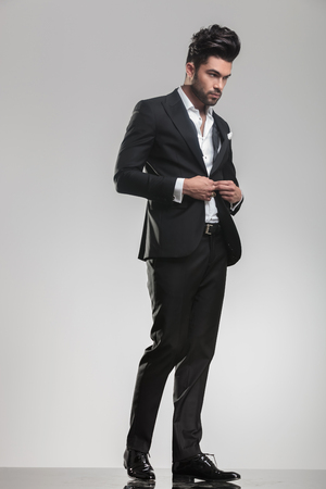 body image: Elegant young man in tuxedo looking away from the camera while closing his jacket, full body image.