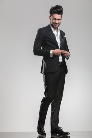Full length picture of an elegant young man in tuxedo, smiling for the camera while closing his jacket.  photo