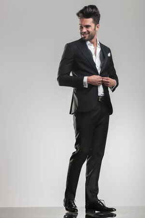 body image: Full body image of an elegant young man closing his tuxedo, smiling while looking away from the camera.