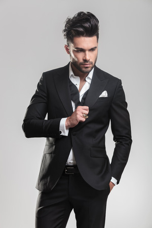 undone: Portrait of an elegant young man in tuxedo looking down while ajusting his tuxedo, holding one hand in his pocket. On grey background. Stock Photo
