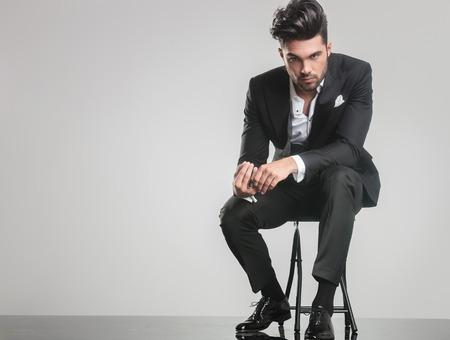 Элегантный молодой человек в смокинге, сидя на стуле, держа палец, глядя на камеру.