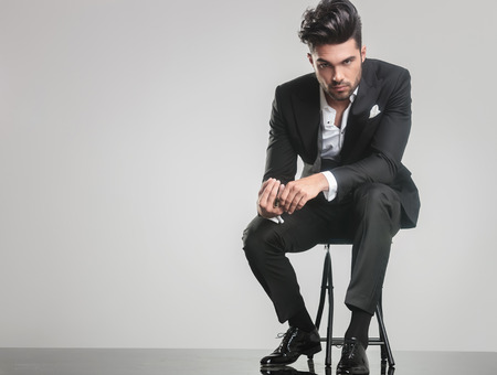 stool: Elegant young man in tuxedo sitting on a stool while holding his finger, looking at the camera.