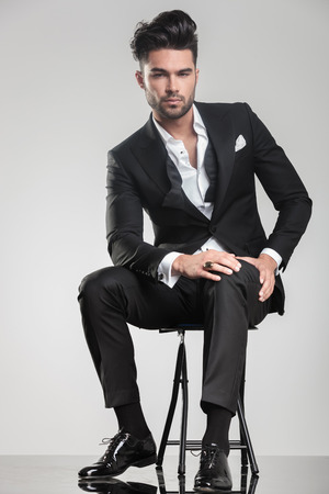 tux: Handsome young man sitting on a stool, holding one hand on his knee while looking at the camera.