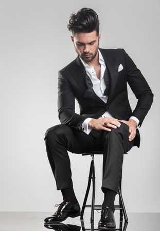 stitting: Elegant young man in tuxedo stitting on a stool while looking down, holding one hand on hei knee. Stock Photo