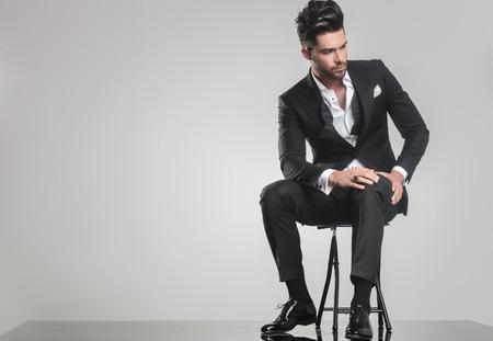 Beeld van een elegante jonge man in smoking op een kruk, op zoek weg van de camera terwijl een hand op zijn knie.