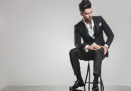 sit: Picture of an elegant young man in tuxedo sitting on a stool, looking away from the camera while holding one hand on his knee.