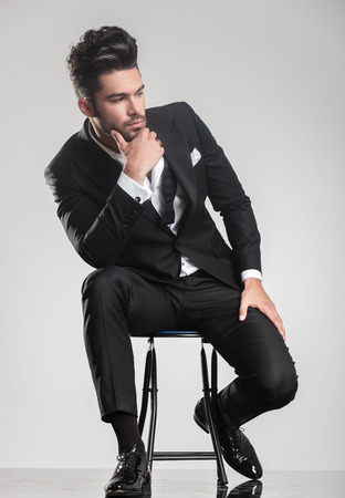 the stool: Elegant young man in tuxedo sitting on a stool, looking away from the camera, thinking and holding one hand to his chin.