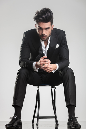 Elegant fashion man in tuxedo looking at the camera while sitting on a stool, holding his hands. photo