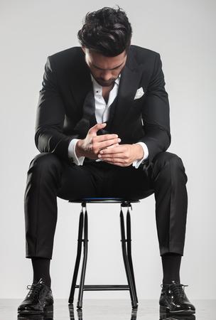 Hombre joven elegante en smoking mirando hacia abajo mientras está sentado en un taburete, sobre fondo gris studio. Foto de archivo